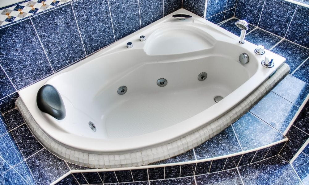 Image-Of-Corner-Whirlpool-Bath-with-Blue-Tiles-Around