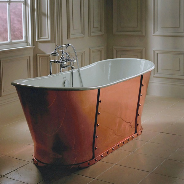 free standing copper bath no legs in a bedroom in front of a window with free standing tap and stand pipes