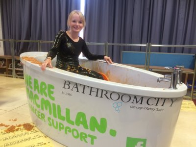 lady in a Bathroom city bath full of beans for Macmillan cancer charity event