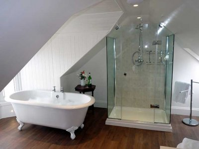 roll top freestanding bath with a 3 sided shower and exposed shower in a bathroom with a sloping roof