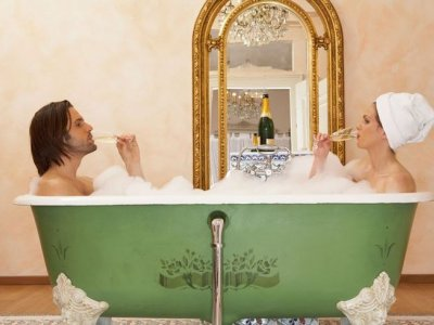 Two people sitting in a double ended freestanding bath sipping campaign