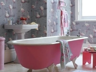 pink free standing cast iron bath on legs in a flamingo wall papered bathroom
