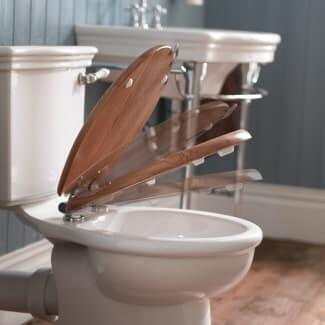 Room Scene View of a Traditional Close Coupled Toilet with Closing Wooden Seat