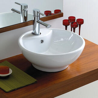 round bathroom wash basin sitting on a wooden work surface